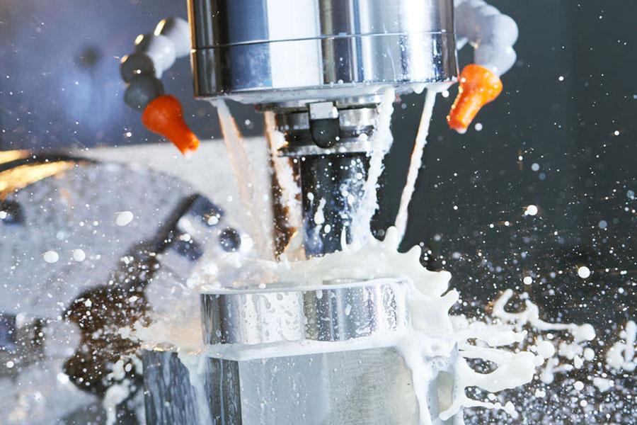 Olio lubrorefrigerante sulla superficie di una fresa mentre lavora un pezzo in metallo